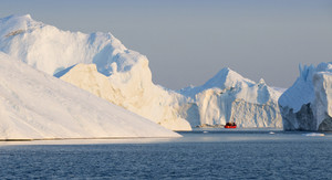 Red boat traveling past sunlit icebergs