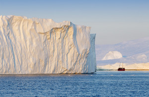 Red boat traveling past a sunlit iceberg