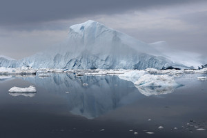 Iceberg reflected in icy waters under a stormy sky