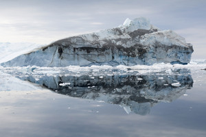 Iceberg reflected in icy waters under a misty sky