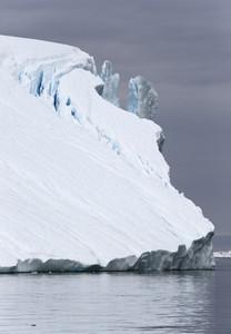 Towering iceberg under a grey sky