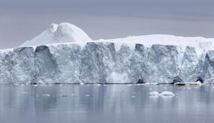 Towering iceberg in icy waters under a grey sky