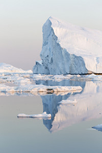 Sunlit iceberg reflected in calm waters