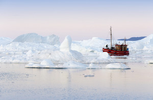 Red boat traveling past an iceberg and ice floe along the coast at dawn