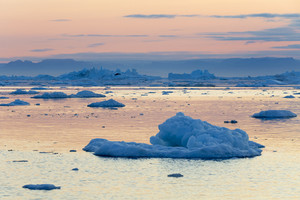 Iceberg and ice floe along the coast during a colorful sunset
