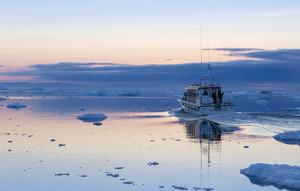 White boat traveling past an iceberg and ice floe along the coast at dusk