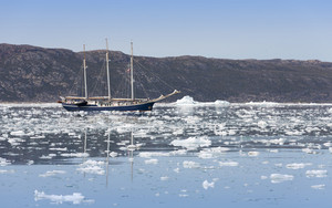 Sailboat traveling icy waters along the coast