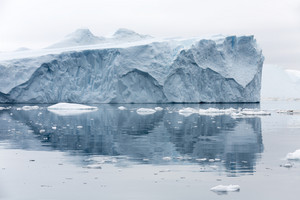 Iceberg reflected in icy waters under a grey sky