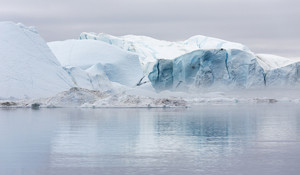 Towering icebergs under a grey sky
