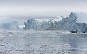 Icebergs in icy waters under a grey sky