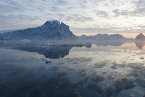 Icebergs reflected in calm waters under a cloudy sky