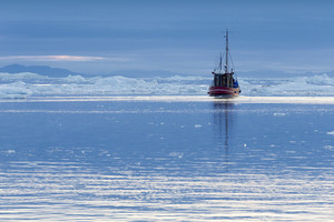 Red boat traveling past ice floes along the coast at dawn