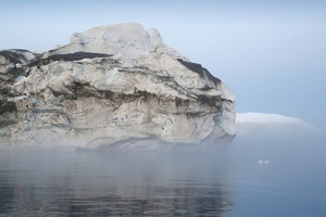 Dirt-streaked iceberg on a foggy day