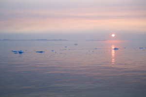 Misty sunrise over the icy ocean and the coast