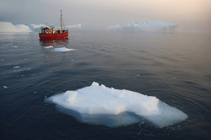 Red boat traveling past an iceberg and ice floes at dawn