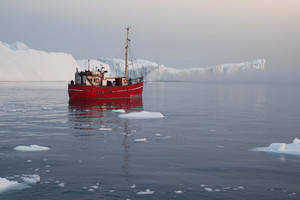 Red boat traveling past an iceberg in icy waters on a foggy day