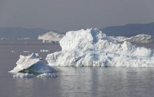 Iceberg and ice floe along the coast on a foggy day