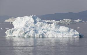White boat traveling past a sunlit iceberg along the coast
