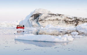 Red boat traveling past a dirt-streaked iceberg in icy waters