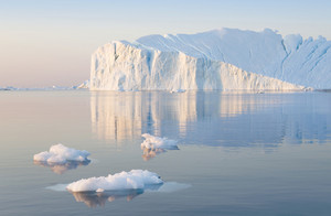 Iceberg and ice floe reflected at dawn