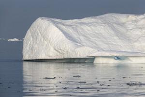 Sunlit iceberg reflected under a grey sky