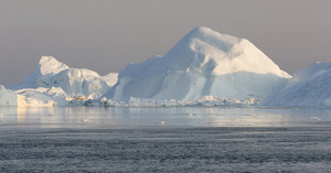 Sunlit iceberg in icy waters under a grey sky