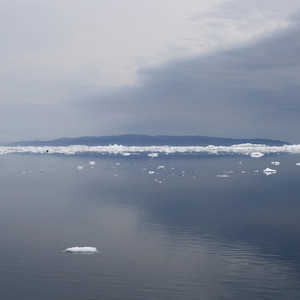 Distant ice floes along a mountain coast under a stormy sky