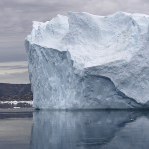 Iceberg reflected in icy waters along the coast against a cloudy sky