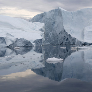 Iceberg reflected in icy waters against a cloudy sky