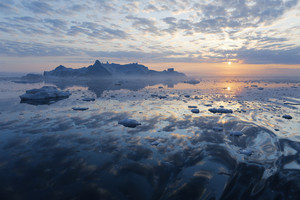 Iceberg and ice floes under a sunset