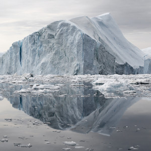 Iceberg and ice floes under a grey sky