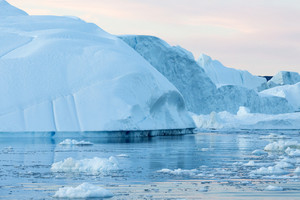 Icebergs and ice floe in icy waters at dawn
