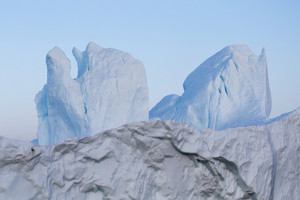 Iceberg with twin peaks against a blue sky