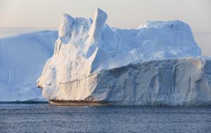 Sunlit iceberg under a grey sky