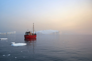 Red boat traveling past an iceberg during a foggy dawn