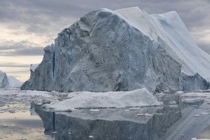 Icebergs and ice floe reflected in icy waters under a stormy sky