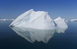 Sunlit iceberg reflected under a blue sky