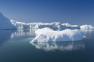 Sunlit icebergs reflected under a blue sky