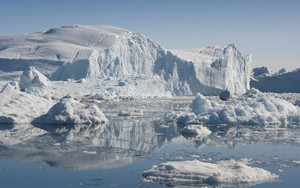 Sunlit iceberg and ice floes in icy waters