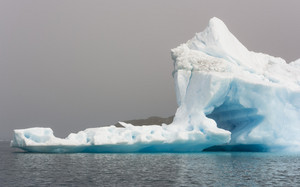 Close up of a sunlit iceberg with a unique hole along a foggy coast