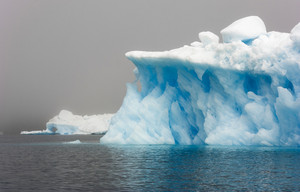 Close up of a sunlit iceberg along the foggy coast