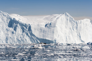 Sunlit iceberg in icy waters under a blue sky