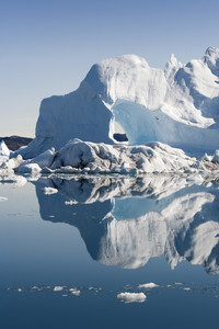 Sunlit icebergs and ice floe reflected at dawn