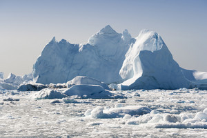 Sunlit icebergs and ice floe in icy waters at dawn