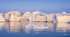 Sunlit iceberg and ice floe under a blue sky