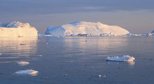 Sunlit icebergs under a grey sky