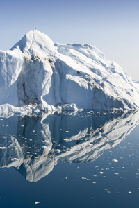 Sunlit iceberg and ice floe reflected in icy waters at dawn