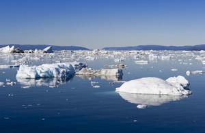 Sunlit iceberg and ice floe along the coast at dawn
