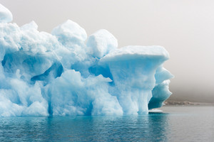 Close up of a sunlit iceberg in dense fog