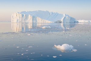 Sunlit iceberg and ice floe reflected in icy waters at sunset